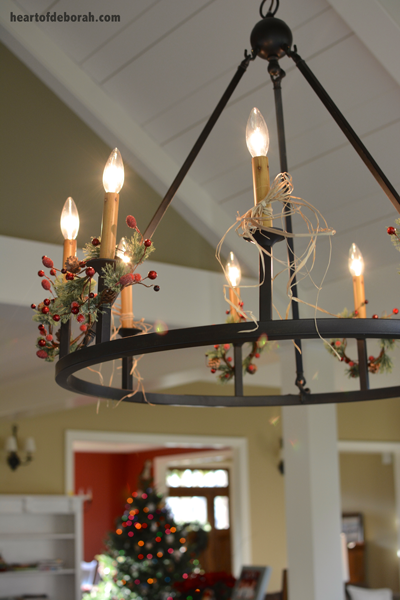 Simple and affordable Christmas decorations. Add mini candle wreaths to light fixture!