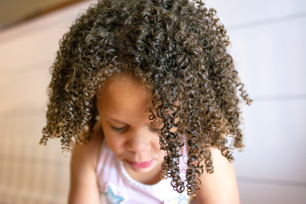 Not sure how to care for your child's gorgeous curls? With these 7 tips for curly hair care in kids learn how to maximize curl definition and embrace your child's naturally curly hair! #curlyhair #devacurl #biracialhair #mixedhair #curls