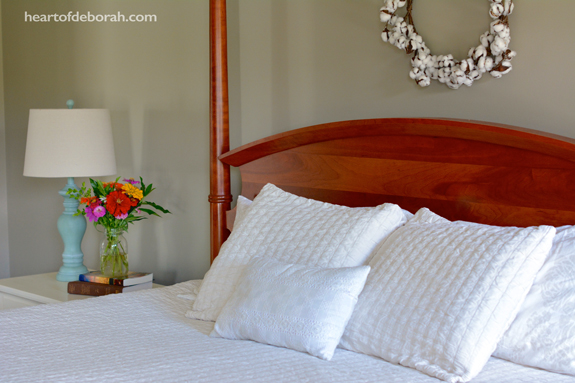 Farmhouse bedroom style. Isn't the cotton wreath beautiful above the poster bed?