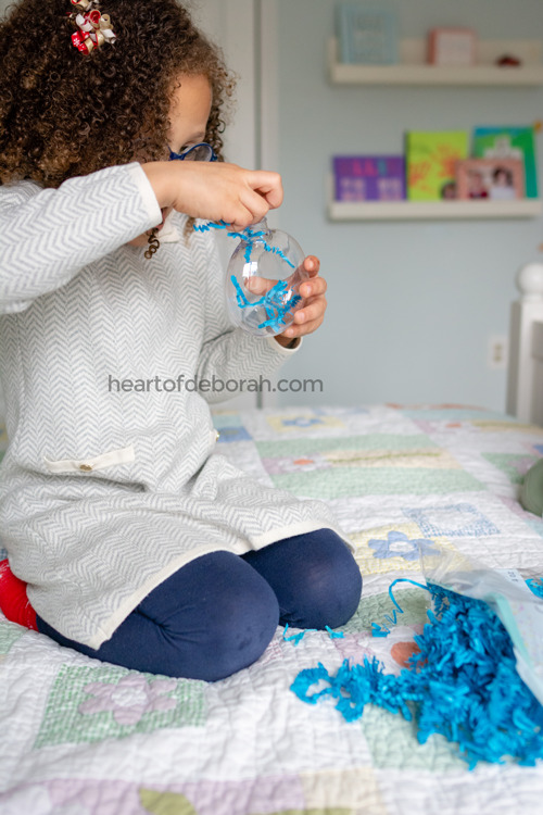 What an easy Christmas craft to do with your kids! They can fill their own plastic ornament with crinkle paper.